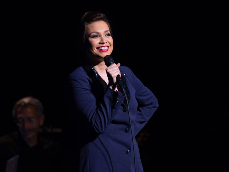 Lea Salonga performing with a microphone in hand