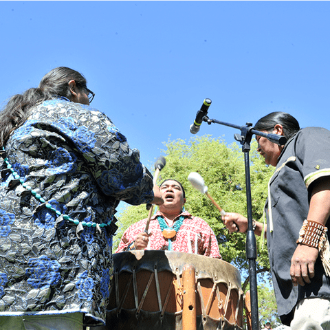 Three performers on a drum outside