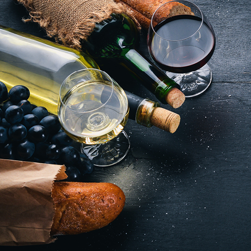 A glass or red wine and white wine with bread and grapes