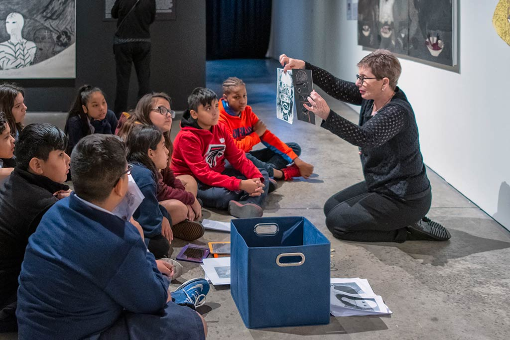 A women teaching young students about art