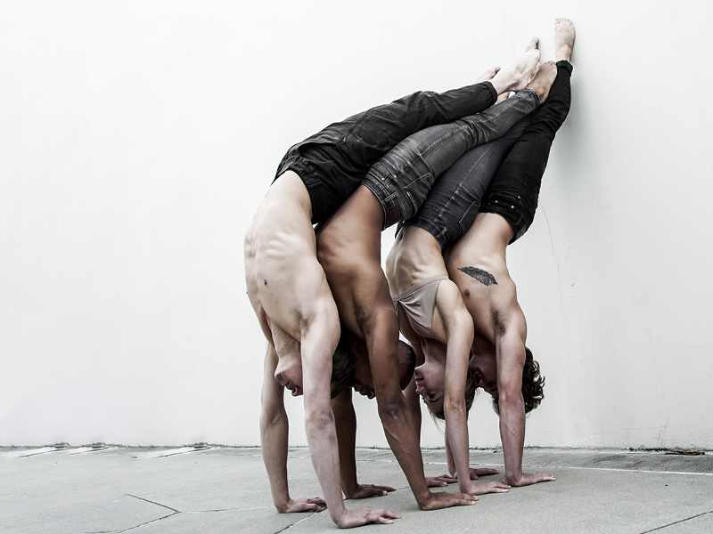 A group of dancers balancing against a wall