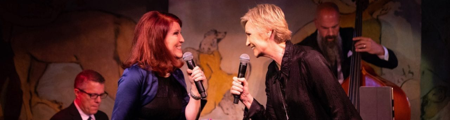 Jane Lynch performing with another women