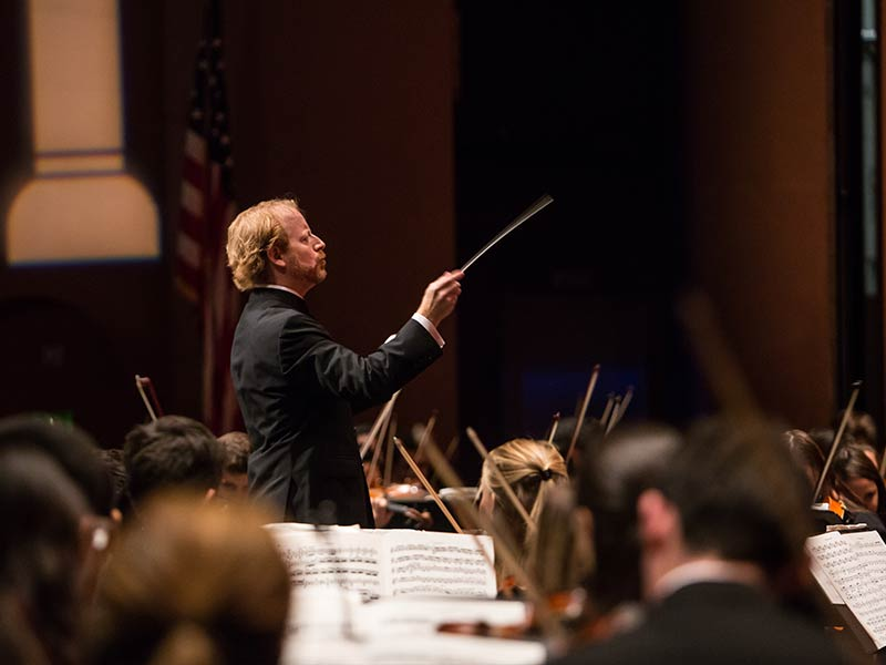 Symphony conductor on stage with orchestra
