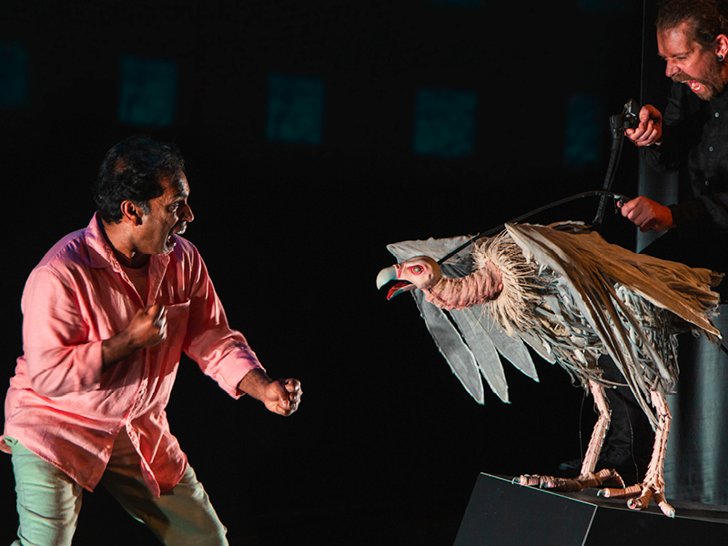 """Production image from Indian Ink Theatre Company """"Paradise or The Impermanence of Ice Cream"""" of a performer on stage next to a puppet."""