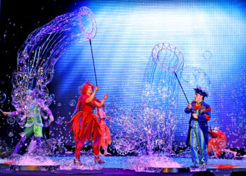 Group of performers on a stage surrounded by bubbles.